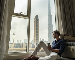 young man in the morning wake up with coffee and a view over Dubai city, Young man by the window of is hotel looking over the city downtown Dubai,Traveler concept or Business concept