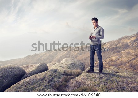 Young man in the mountains using a mobile phone