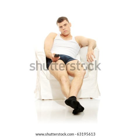 Young man in underwear, sitting in armchair with remote control in hand - bored. Isolated on white