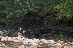 Young man in uniform and cap sitting on big stone while fishing at mountain river. Professional fisherman enjoying favorite hobby on fresh air.