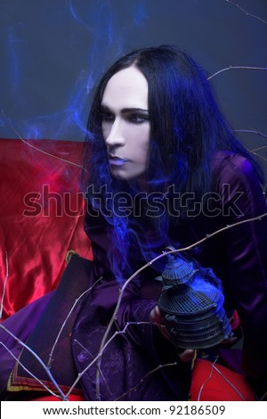 Young man in violet chinese costume sitting on the sofa - stock photo