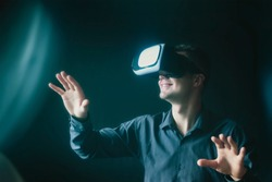 Young man in virtual glasses sees virtual reality.