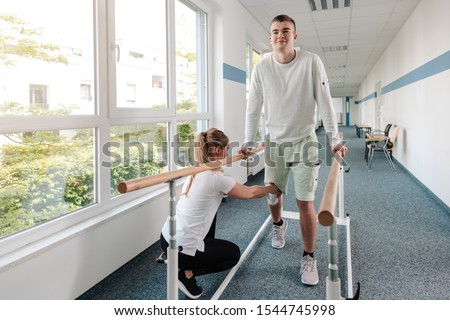 Young man in walking rehabilitation course after a sport injury on his knee ストックフォト ©