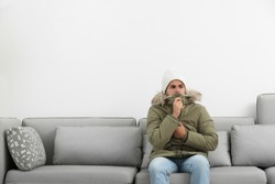 Young man in warm clothes freezing on sofa against white background