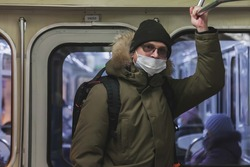 Young man in wear casual winter clothes with glasses and medical mask in metro wagon. Attractive teenager with backpack in big city subway, looking at camera and emotions of an unexpected encounter