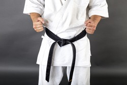 Young man in white kimono and black belt training martial art over gray background