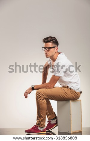 young man in white shirt looking away while seated on a box