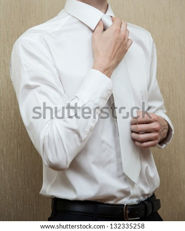 Young man in white shirt straightenes his tie
