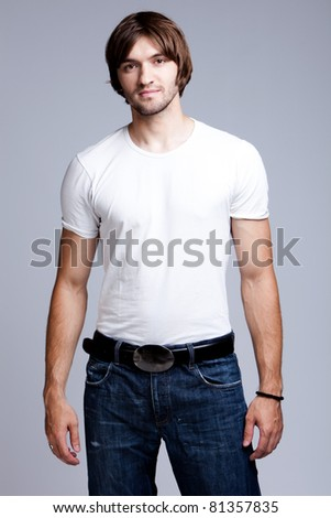 young man in white t-shirt and jeans, studio shot