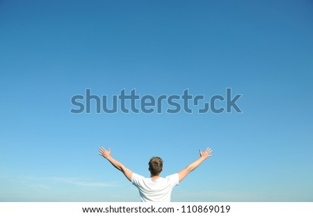 Young man in white t-shirt, arms open and blue sky / The world is open