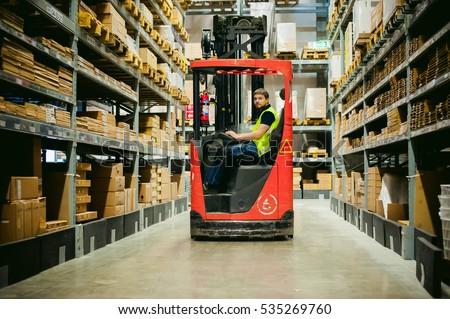 young man in working clothes, driver Reachtruck busy working on the logistics warehouse store