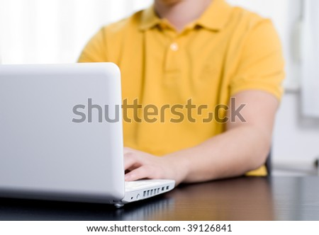 Young man in yellow shirt types on notebook (shallow DOF, focus on lid)