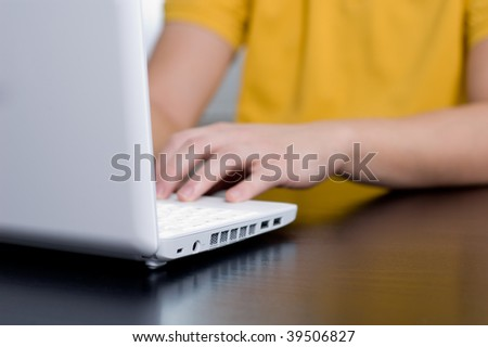 Young man in yellow shirt types on notebook (very shallow DOF, focus on power port)