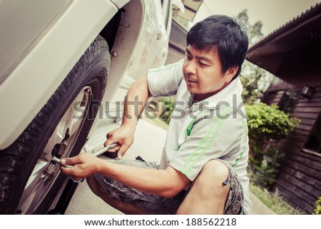 Young man is changing tire of he car with wheel wrench. process color