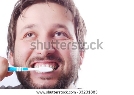 Young man is cleaning his teeth with brush