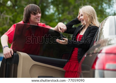 Young man is giving car key to his girlfriend