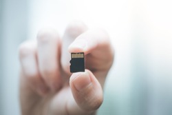 Young man is holding a tiny memory card in his hand, text space