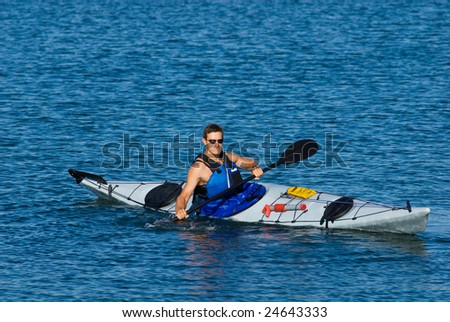 Young man is kayaking in calm blue waters of Mission Bay, San Diego, California. Copy space on top.