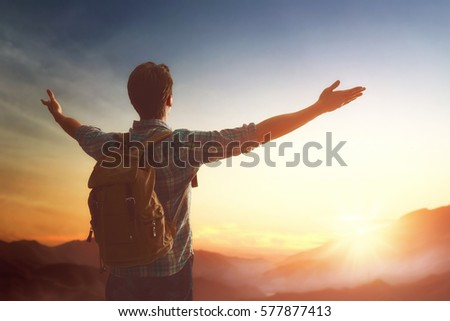 Young man is looking at sunset. Traveller with backpack. #577877413