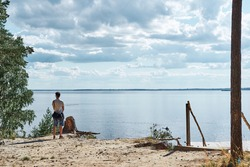 Young man is looking at the beautiful sea with clouds near forest trailway, Weekend activities in summer