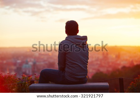 Young man is looking at the sunrise.