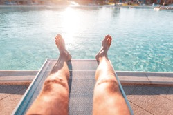 Young man is lying and rest on a beach lounger near swimming pool with blue water at sunset. Male tanned legs relax and Sunbathes, close-up. Summer vacation concept.