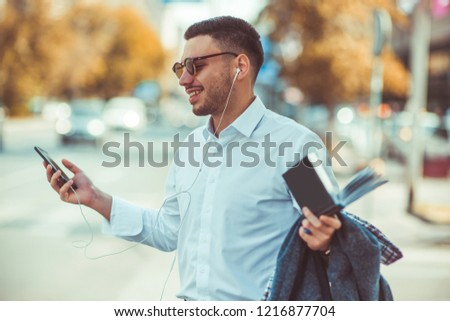 Young man is outdoors at the city, he is looking happy while looking at his phone #1216877704