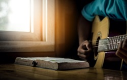 Young man is playing guitar and sing a song from Christian hymn book with bible on wooden table