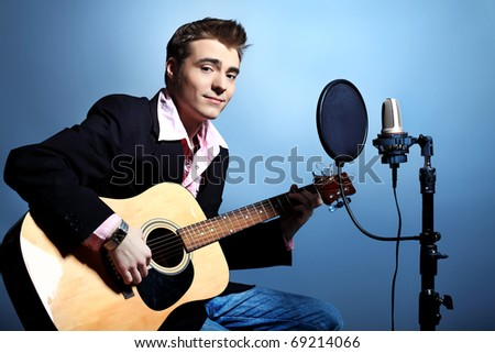 Young man is playing on a guitar at studio, rock'n'roll style.