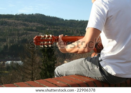 Young man is playing outside, on the roof. Mountain scenery. Mayby he is playing for God and he is worshipping him. He sings.
