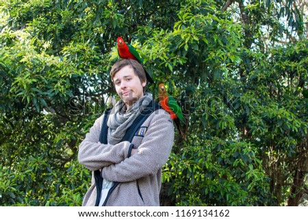Young man is proud of attracting wild parrots