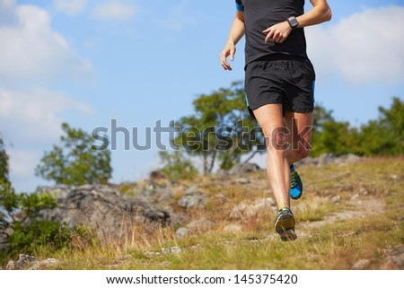 Young man is running in nature - selective focus
