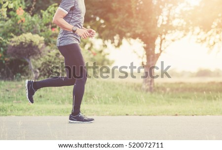 Young man is running on road sunset.