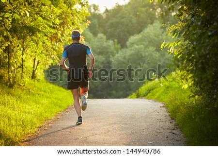 Young man is running on road - sunset back lit