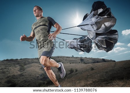 Young Man is Runs in the mountains. Functional Training of the Runner with sports Parachutes. Running with speed resistance. Workout outdoors.