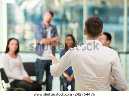 Young man is sharing his problems with people. View of man is telling something and gesturing while group of people are sitting in front of him and listening.
