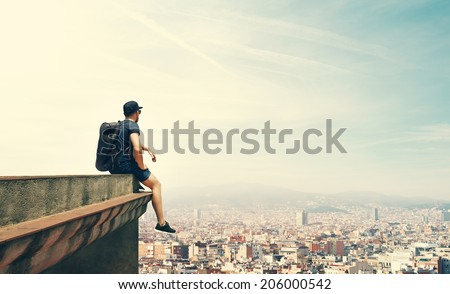 Young man is sitting on a roof and looking city #206000542