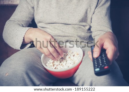 Young man is sitting on a sofa and eating popcorn while watching television Сток-фото ©