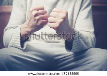 Young man is sitting on a sofa with his fists clenched
