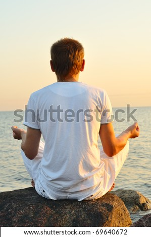 young man is sitting on a stone and looking at sea sunrise. view from behind