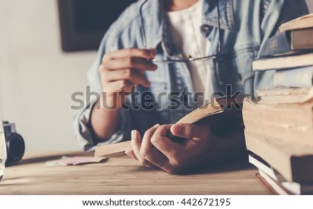 Young man is sitting on table and reading a book
