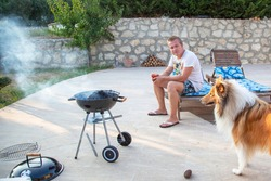 Young man is sitting with glass of tomato juice and looking on his Scottish collie ginger dog and guy is waiting for grill to be ready, hot to cook