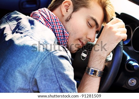 Young man is sleeping in a car.