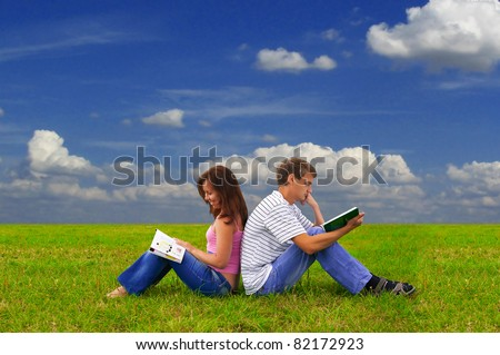 young man is studying a book while girl is reading a magazine