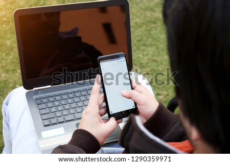 Young man is using smartphone with laptop.