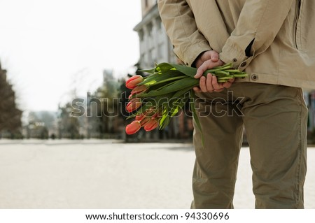Young man is waiting for his girlfriend with tulips