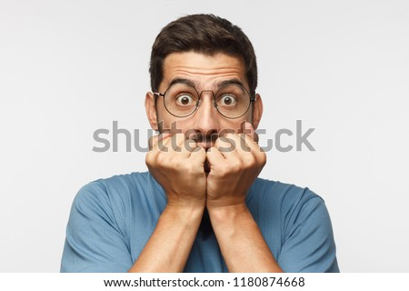 Young man isolated on gray background, covering mouth with hands and round eyes, wearing round eyeglasses, experiencing deep astonishment and fear #1180874668