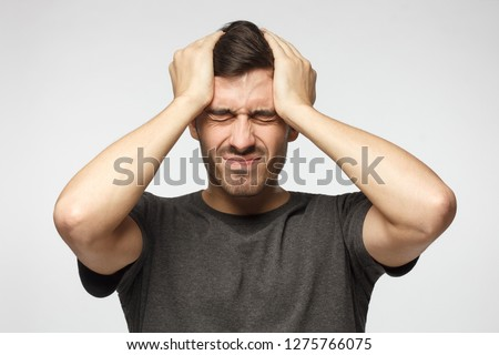 Young man isolated on gray background, showing how much head hurts, experiencing pain, looking miserable and exhausted. Headache concept.