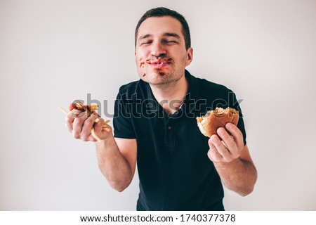 Young man isolated over white background. Satisfied happy guy with ketchup all around his mouth smiling. Hold burger and french fries in hands. Glutton man on picture.