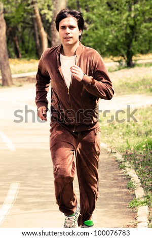 young man jogging through wood spring day